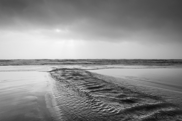 Stream-running-into-the-sea-on-Charmouth-Beach-27_12_15-b&w