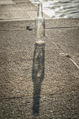 Sunlight-on-beer-bottle-on-Main-Beach-seawall,-Lyme-Regis-09_11_14-2