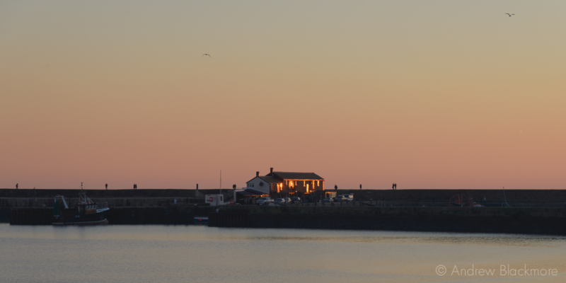 The-setting-sun-reflecting-off-the-Cobb-buildings-from-Front-Beach,-Lyme-Regis-29_12_14-2-pan