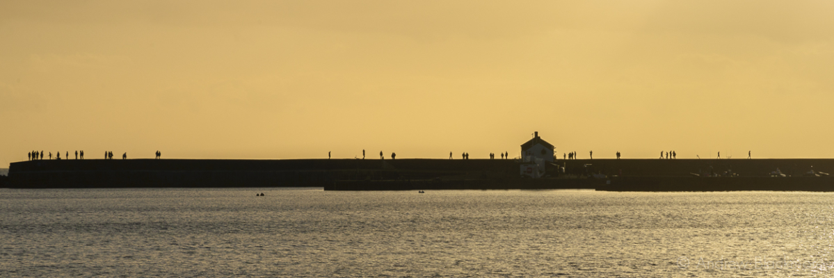 Walkers-silhouetted-on-the-Cobb,-Lyme-Regis-02_01_15-1-2-pan