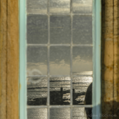 Sunlit-sea-reflected-in-a-window-of-The-Sundial,-Lyme-Regis-23_11_15-1-sq