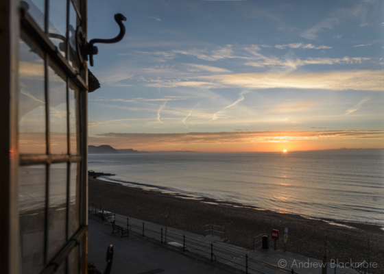 Sunrise-over-Lyme-Bay-through-a-window-in-The-Sundial,-Lyme-Regis-23_11_15-1