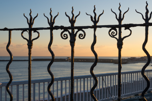 The-Cobb-through-iron-railings-at-sunset-from-Bell-Cliff,-Lyme-Regis-05_11_12
